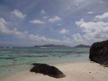 Seychelles la digue, view on praslin blue cristalline water and pink granit rock stock images