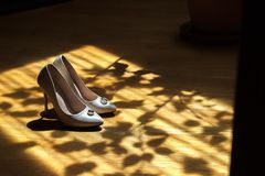 White beautiful wedding shoes in dark shade in sunlight royalty free stock images