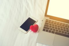 White bed with blank screen for text on smartphone, tablet, cell. White bed with blank screen on smartphone, tablet, cell phone and red heart shape sign royalty free stock photos