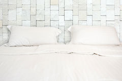 A white bed with 2 pillows in hotel. A white bed with 2 pillows in room Royalty Free Stock Image