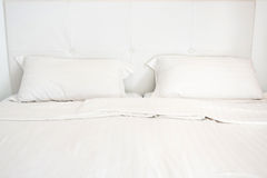 A white bed with 2 pillows. In room Stock Photo