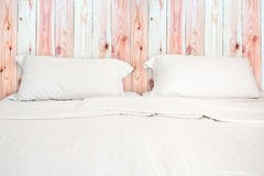 A white bed with 2 pillows in room. A white bed with 2 pillows in wooden room Royalty Free Stock Images