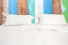 A white bed with 2 pillows on wooden wall room. Background Royalty Free Stock Image