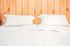 A white bed with 2 pillows on wooden wall room. Background Stock Photos