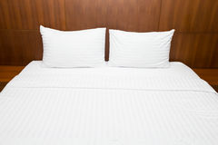 White bed sheets and pillows Stock Images