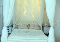 White bed and shining lights in bedroom.  Stock Photography