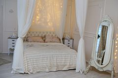 White bed and shining lights in bedroom.  Stock Images