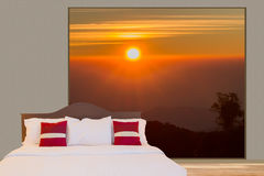 White bedding sheet and pillows on the bed in a room with big window see through sunset over mountain view Stock Photos