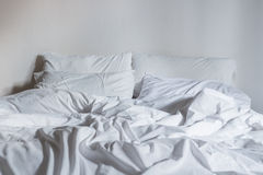 White bedding sheets and pillow, Messy bed concept Royalty Free Stock Photography