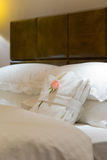 White bedgown with rose on bed Stock Image