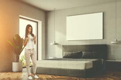 White bedroom corner, poster, woman. Woman in a white bedroom interior with a wooden floor, a master bed and a horizontal poster hanging above it. A side view 3d Stock Photos