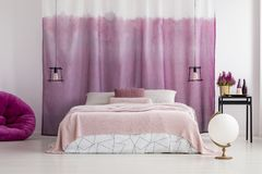 White bedroom with pink accents. White bedroom interior design with pink accents and fabric hanging behind king-size bed Stock Photography