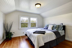 White bedroom interior with queen size bed. Bedroom with wood plank paneled walls and ceiling. View of black queen size bed and dry branches in the corner stock photo