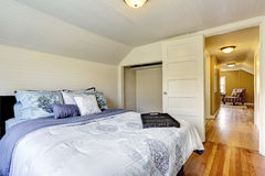 White bedroom interior with queen size bed. Bedroom with wood plank paneled walls and ceiling. View of black queen size bed and small closet stock images
