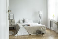 White bedroom interior in real photo with king-size bed with kni stock photography