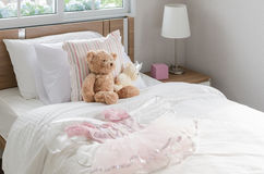 White bedroom with pillows and doll Stock Photo