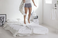 The white bedroom. Woman with a blanket jumping on a bed. royalty free stock photography
