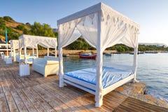 White beds on the public beach of Crete. White luxury beds on the public beach of Crete, Greece Stock Photos