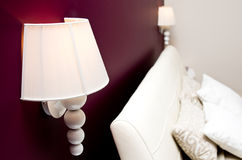 Modern bedroom. White bedside lights and headboard on a burgundy red wall Stock Photography