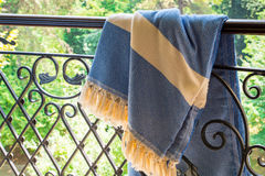 A white beige and blue Turkish peshtemal / towel on a wrought iron railings with blurry nature in the background. Stock Photo