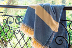 A white beige and blue Turkish peshtemal / towel on a wrought iron railings with blurry nature in the background. Stock Images
