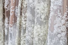 White and beige textile for wedding dresses on shopfront. A lot of fabric rolls. Bolts of white fabric with beadwork. Rows of diverse textiles Stock Photo