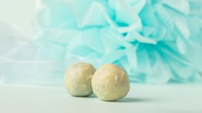 White Belgian chocolate round chocolates on a gentle blue background. Copy space. Selective focus. stock photography