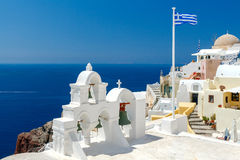 White bell tower and Greek flag in Oia. Royalty Free Stock Images
