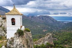 White bell tower. Landscape photo: View over the valleys of Puig Campana in the region of Alicante, Spain royalty free stock photo