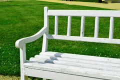 White bench in the background of green grass royalty free stock photo