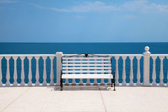 White bench, balustrade and sea Stock Images