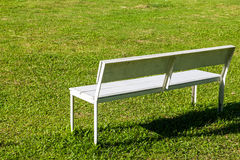 White bench. Empty white bench on the lawn in sunny day stock photos