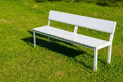 White bench. Empty white bench on the lawn in sunny day stock image