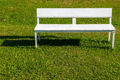 White bench. Empty white bench on the lawn in sunny day stock photography