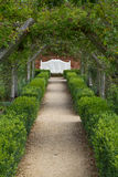 White bench at the end of a path. Manicured garden path ledaing to a white bench Royalty Free Stock Image