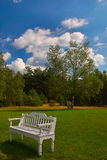 White bench on fresh green grass Stock Images