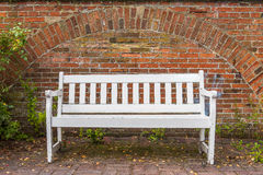 White bench in front of red brick wall , chained to the floor Stock Photography