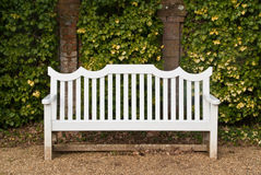 White bench in front of wall Royalty Free Stock Images