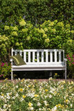 White bench in the lush garden Royalty Free Stock Images