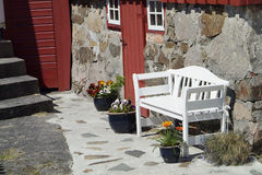 White bench and old house. White, wooden bench and flowers in front of old house Royalty Free Stock Photography
