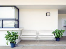 White bench outside of building. Royalty Free Stock Photography