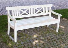 White bench in a park. Photography of a white bench in a park. The photography has been taken in natural day light in May stock images