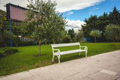 White bench in park with trees and lawn Royalty Free Stock Photo