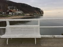 White bench on the pier. White wooden bench with slats next to the railings of the pier overlooking hotels beside the beach at Gdynia, Orlowo, Poland stock photo