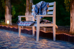 White Bench with Plaid Blankets on Patio at Dusk Royalty Free Stock Image