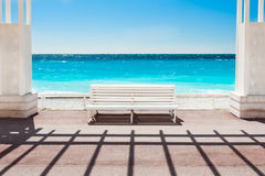 White bench on the Promenade des Anglais in Nice, France. Beautiful turquoise sea and beach royalty free stock photography