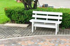 White bench in public garden. Stock Photos