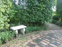 White bench in quiet corner. White garden bench and brick path in the garden royalty free stock image