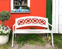 White bench and red house Royalty Free Stock Images