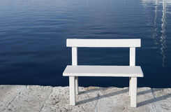White bench for sitting by the sea. Small white empty bench by the sea Royalty Free Stock Photo